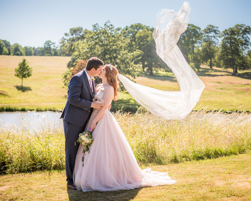 Bride's veil blowing while they kiss in castle grounds, Ripley Castle weddings, Yorkshire wedding photographers