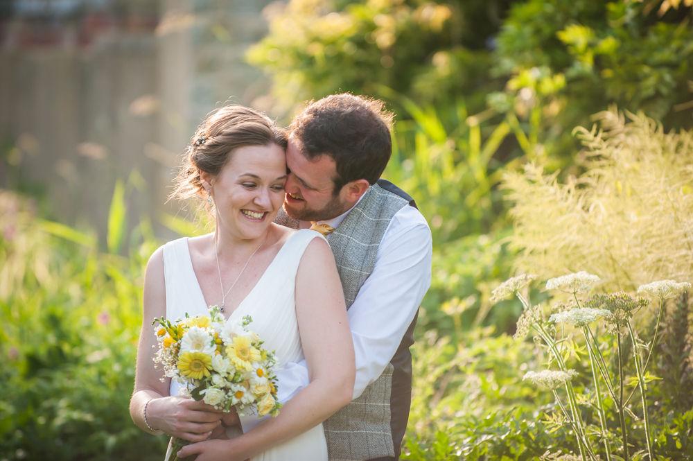 Bride and groom cuddles in hotel garden, Ringwood Hall weddings, Sheffield wedding photographer