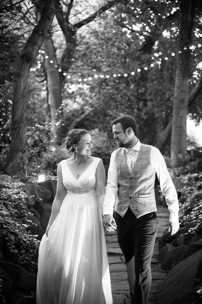 Bride and groom walking through secret garden, Ringwood Hall weddings, Sheffield wedding photographer