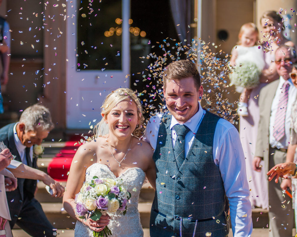 Bride and groom walking through confetti, Wortley Hall, Sheffield wedding photography