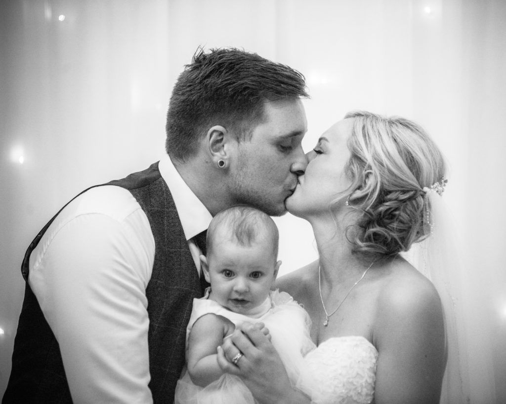 Bride and groom kiss with daughter in the middle, Wortley Hall, Sheffield wedding photography