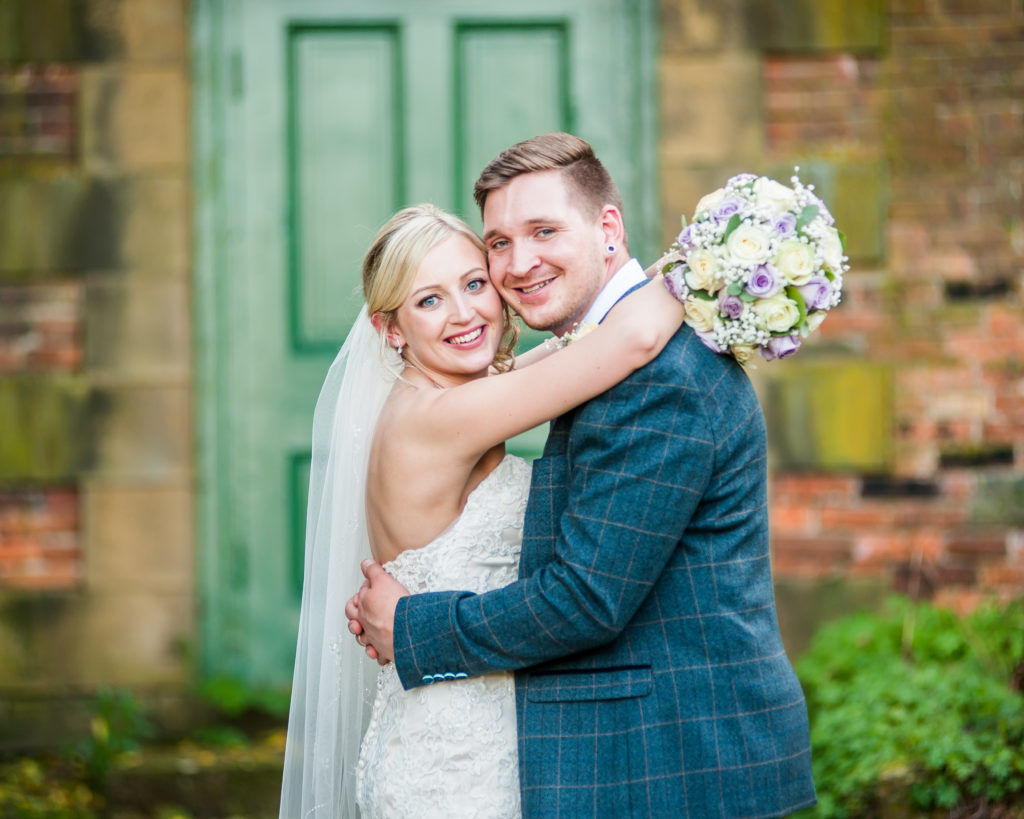 Bride and groom posing by green door in grounds, Wortley Hall, Sheffield wedding photography