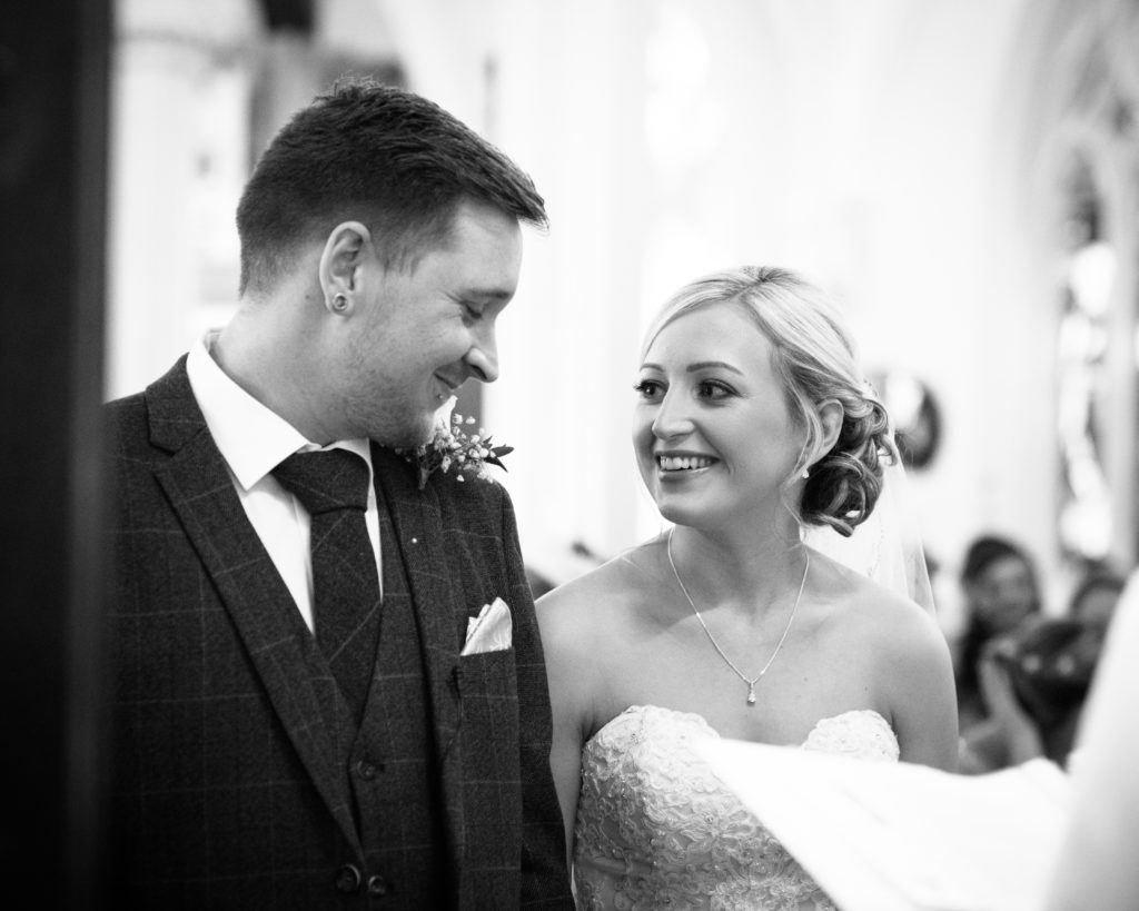 Groom smiling at bride at top of aisle, Wortley Hall, Sheffield wedding photography