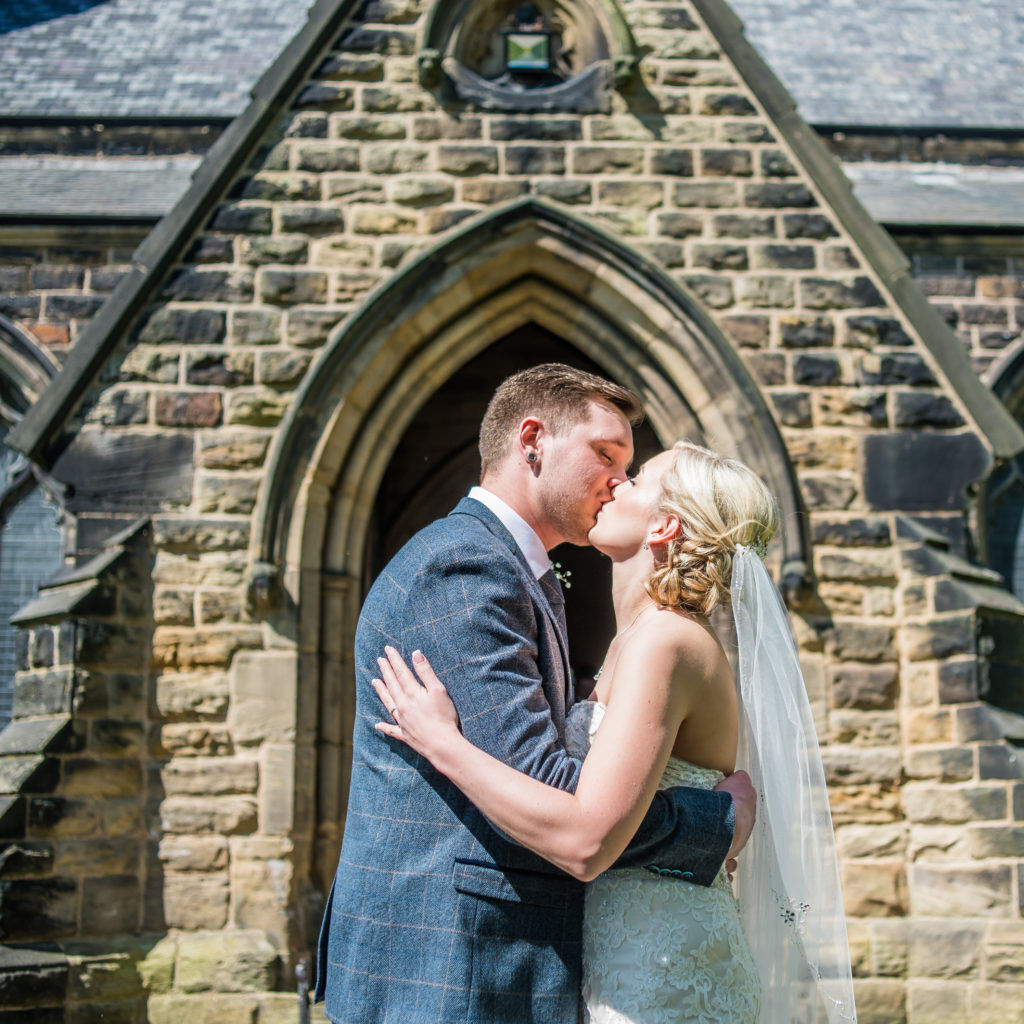 Bride and groom kiss outside church, Wortley Hall, Sheffield wedding photography