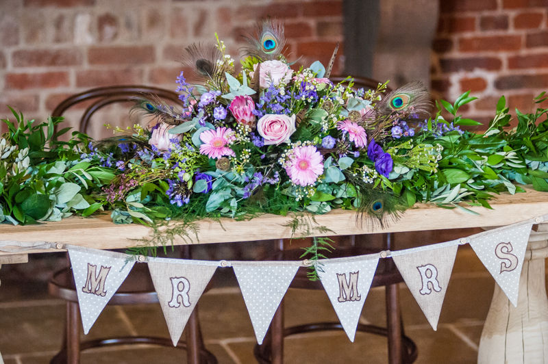 Joelle & Scott's table top flower arrangement with peacock feathers for their Sheffield wedding at Hazel Gap Barn