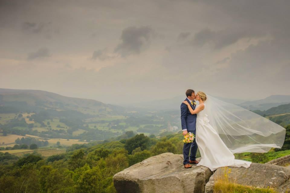 Bride and groom kissing on rocks, Keswick wedding photographers