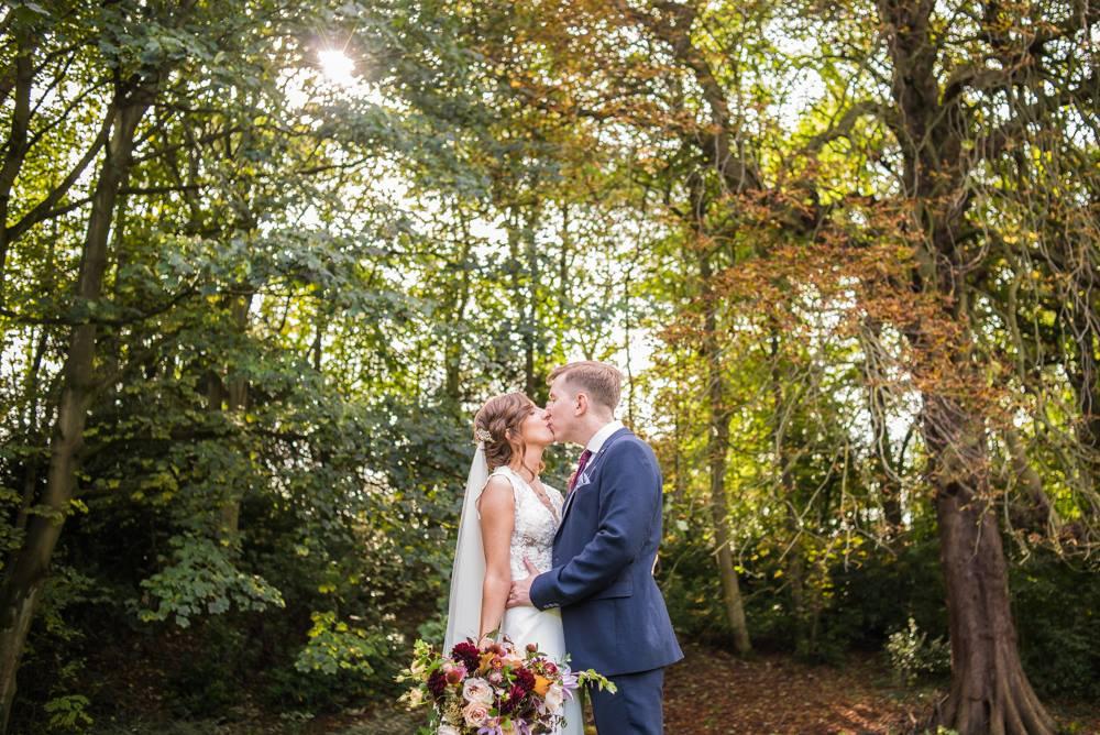 Bride and groom kissing in woods, Carlisle weddings