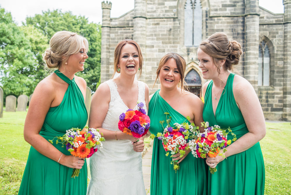 Sheffield wedding photographers, Bridal party laughing outside church in Stannington