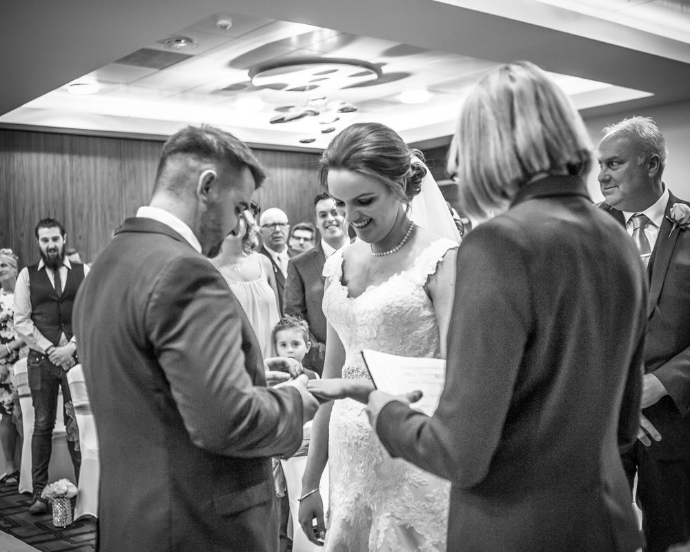 Groom putting ring on brides finger, Chesterfield wedding photographer, Casa Hotel