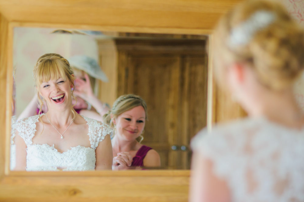 Bride laughing in mirror, Sheffield wedding photographers, Smallshaw Farm Cottages