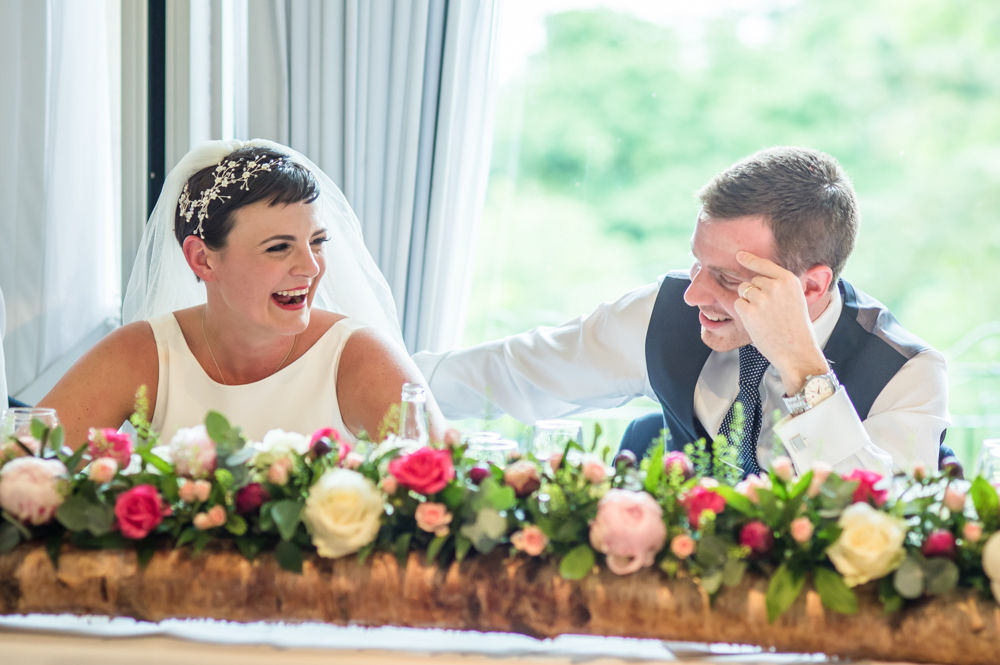 Groom and bride laughing during speeches, Sheffield wedding photographers, Whirlowbrook Hall