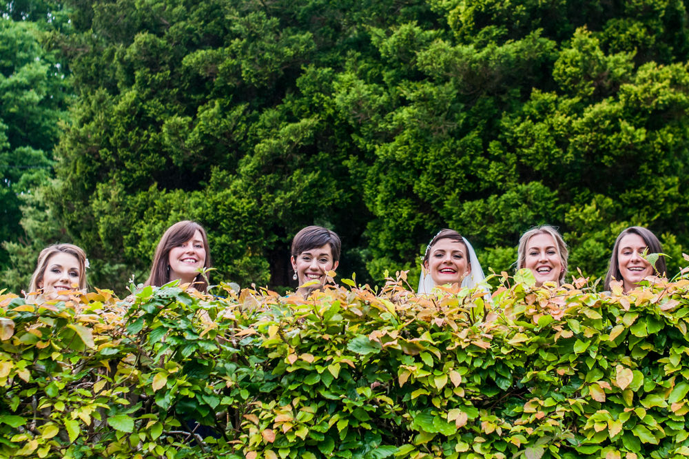 Bride and friends peeping over hedge, Sheffield wedding photographers, Whirlowbrook Hall