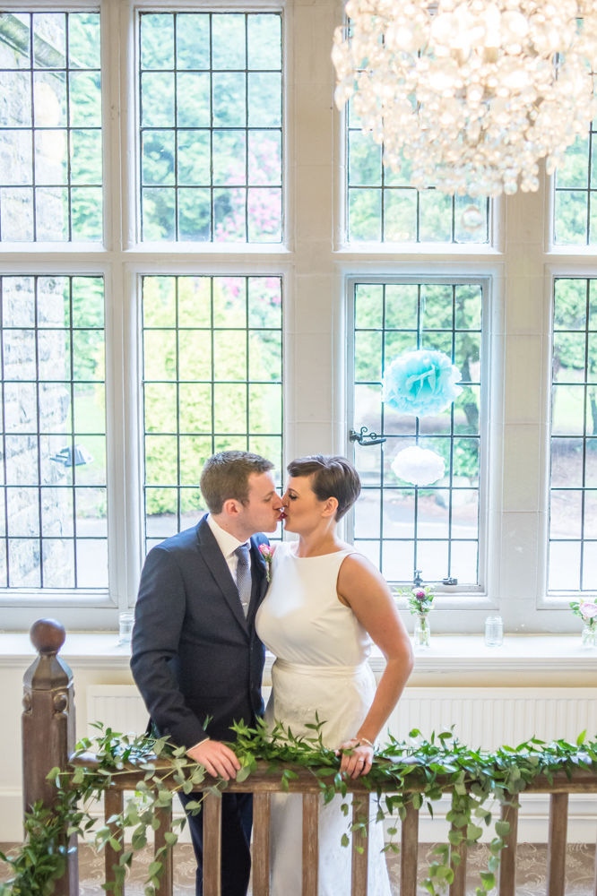 Bride and groom kissing on stairs, Sheffield wedding photographers, Whirlowbrook Hall