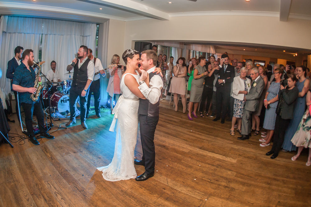 Bride and groom first dance with guests in background, Sheffield wedding photographers, Whirlowbrook Hall