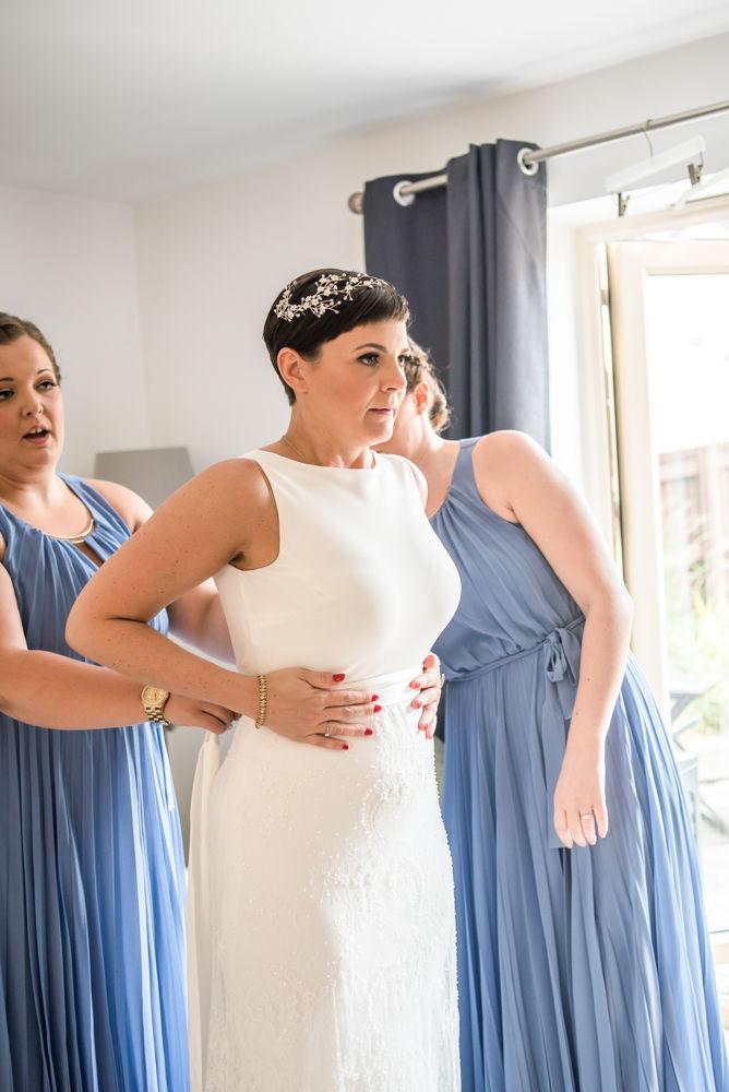 Bride putting dress on with bridesmaids, Sheffield wedding photographer