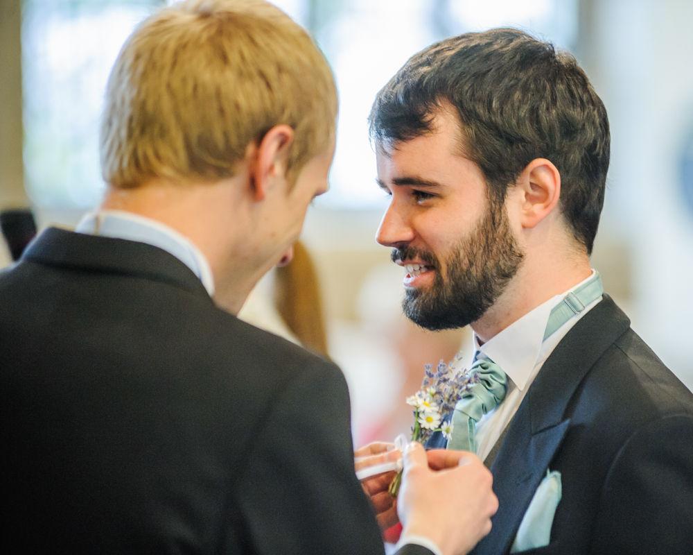 Groom adjusting buttonhole, Sheffield wedding photographers