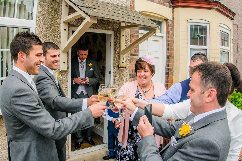Groom and family cheers - Cumbria wedding photographers