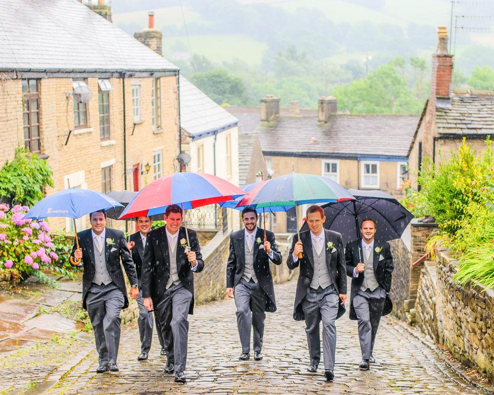 Groomsmen walking to church in rain, Peak District wedding photographers