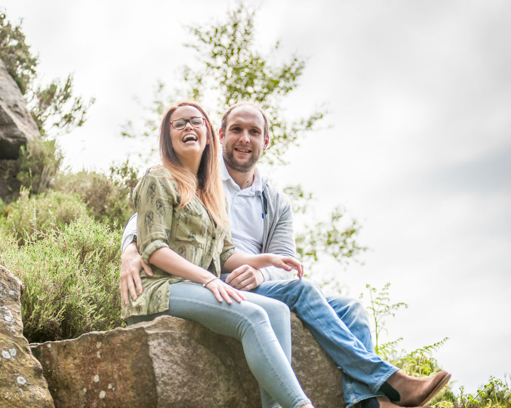 Sitting on top of rock laughing, Peak District wedding