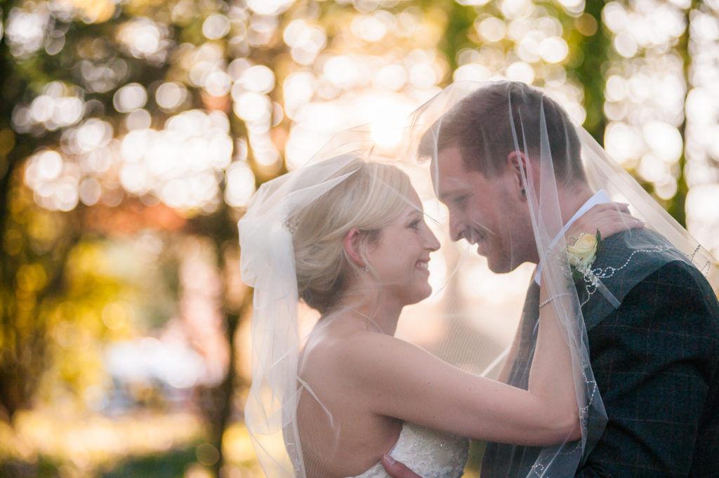 Bride and groom under veil, Cumbria wedding photographers