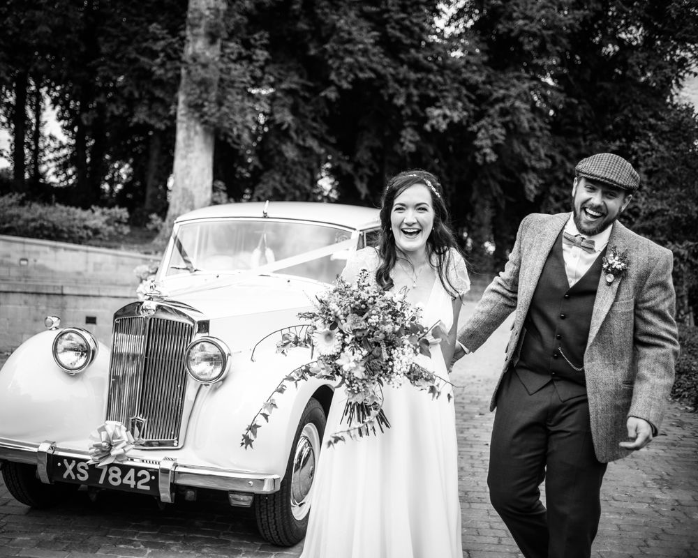 Laughing by wedding car,  Wentworth Castle Garden wedding, Sheffield photographers