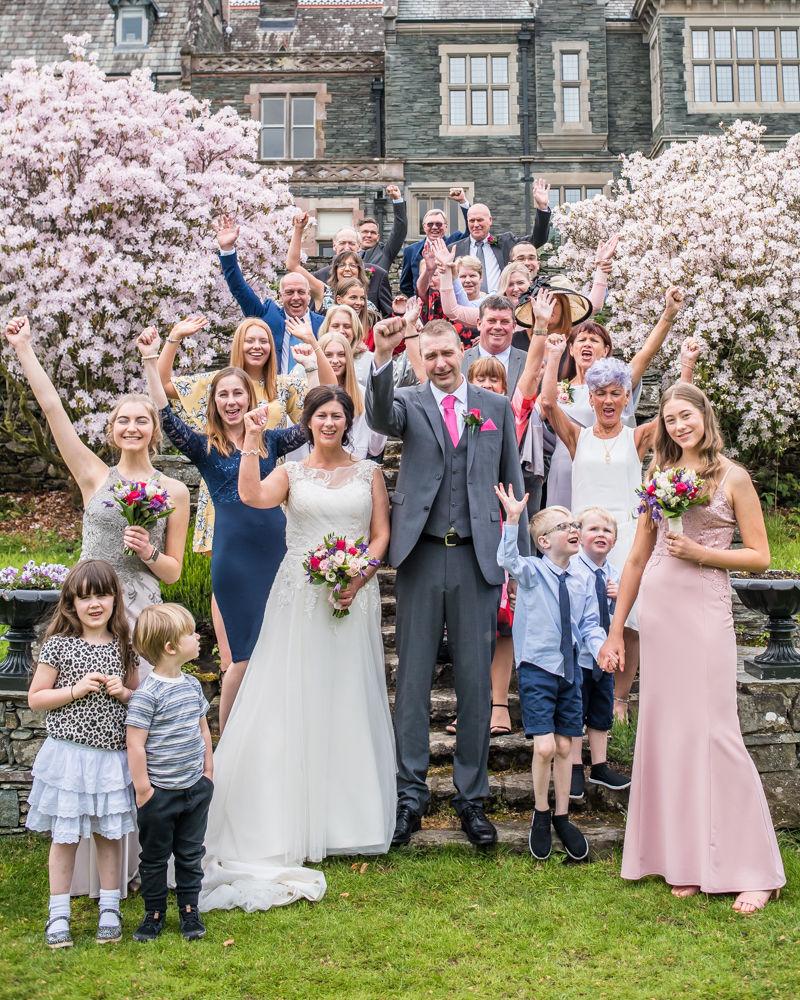 Full group photo waving, Lingholm wedding, Lake District