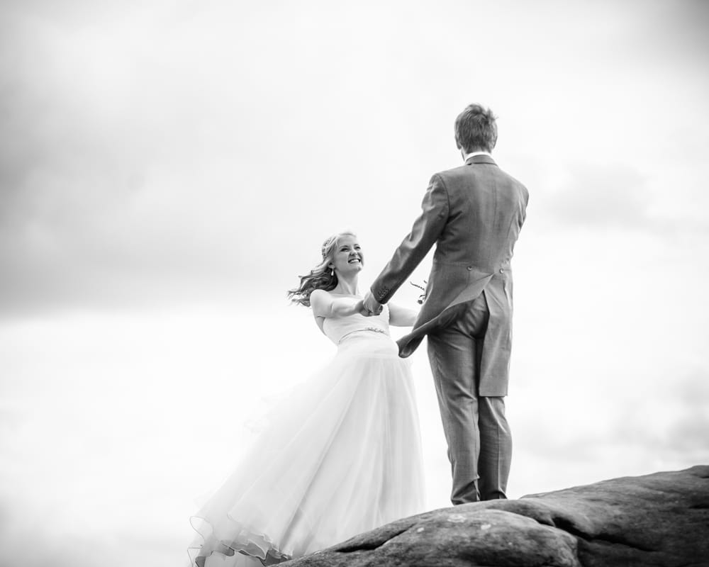 Holding hands on top of Peak District rocks, Maynard wedding, Sheffield photographers