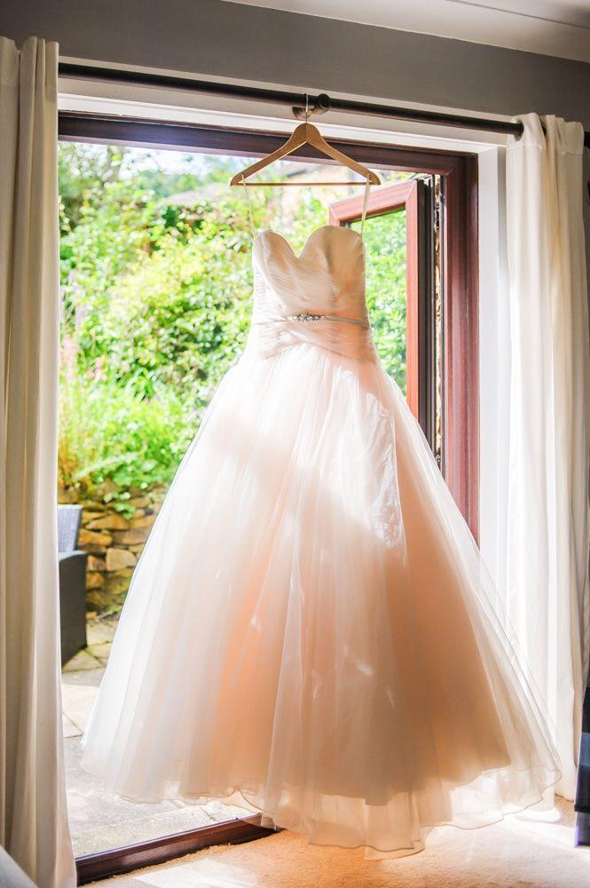 Emma's wedding dress hanging in window, Maynard wedding, Sheffield photographers