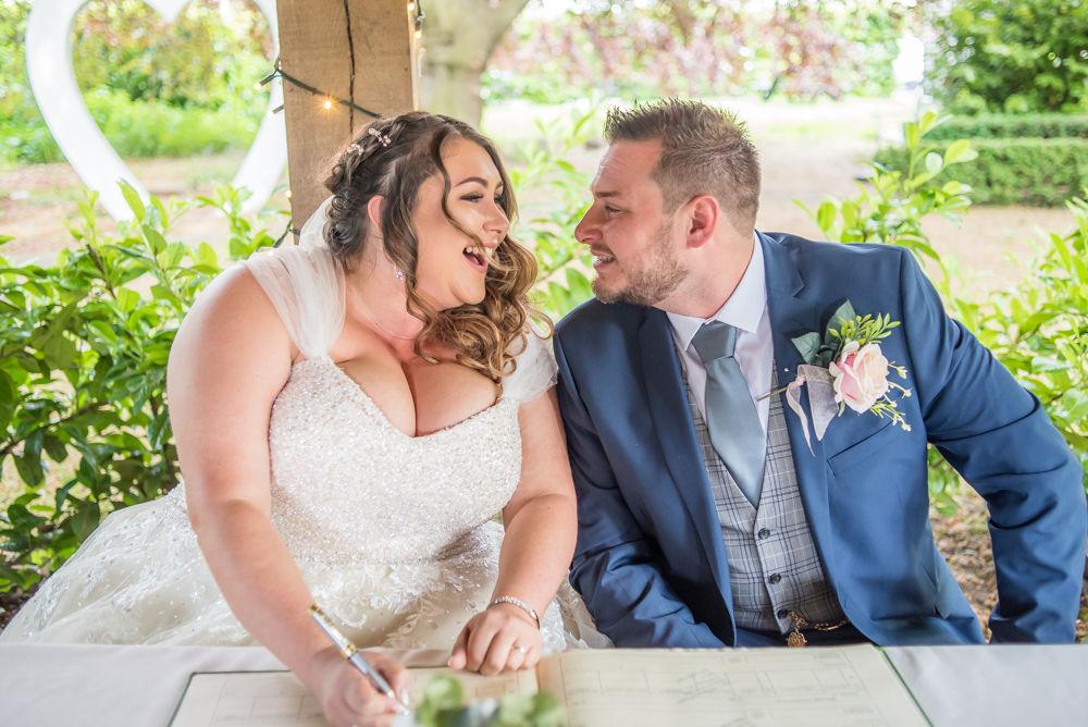 Laughing during register signing, Ye Olde Bell wedding, Retford