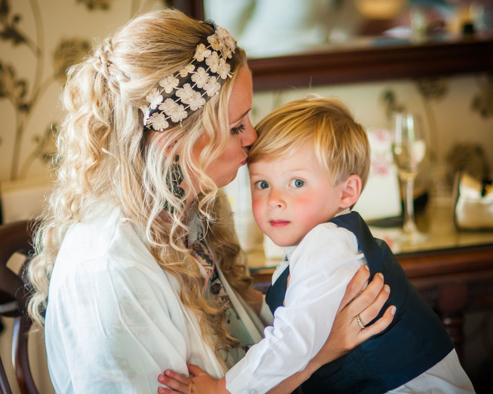 Bride cuddling her son, Overwater Hall wedding, Lake District