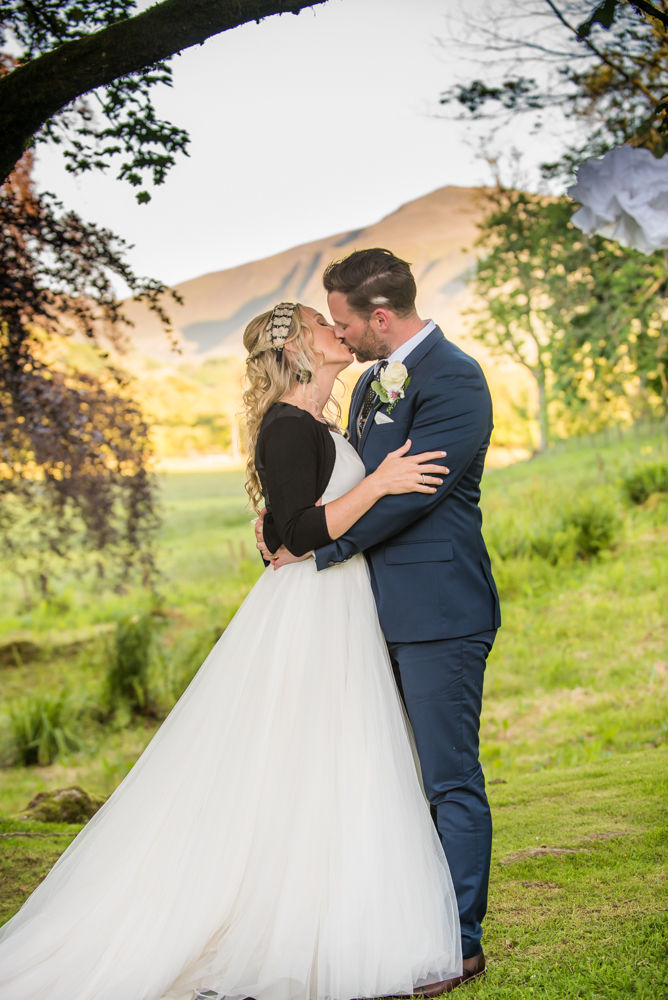 Kissing at sunset with views of fells, Overwater Hall wedding, Lake District