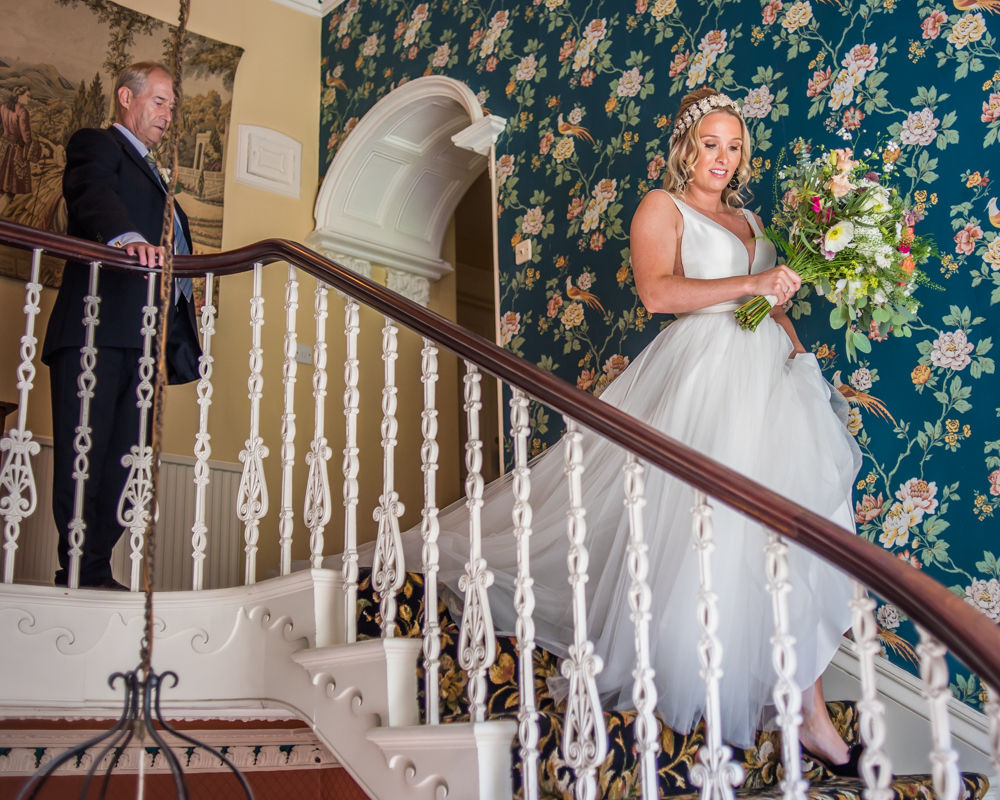 Bride walking down staircase, Overwater Hall wedding, Lake District