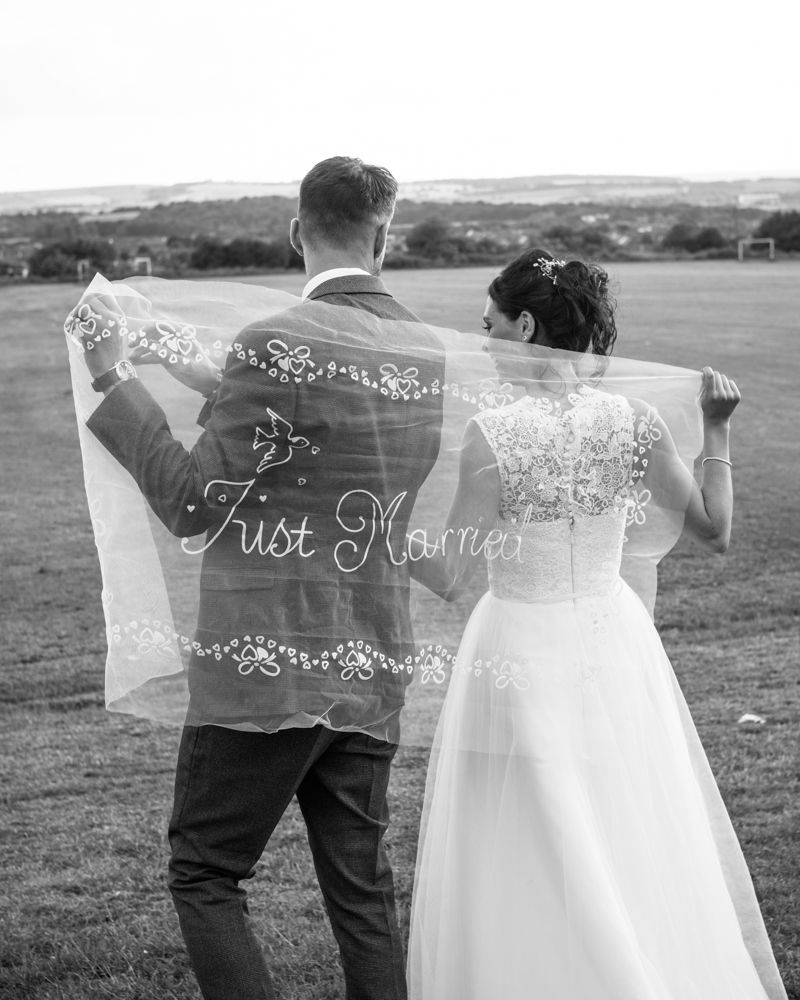 Bride and groom walking with Just Married sign. Yorkshire weddings