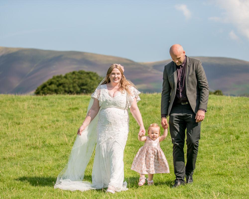 Bride and groom walking to lake, Derwentwater Rock the Dress, Lake District wedding photographer