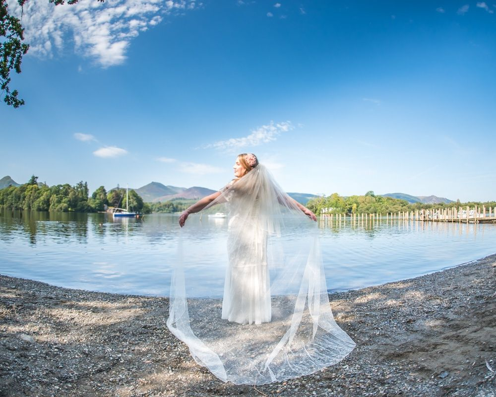 Posing, behind view of wedding dress with Lake in background, Derwentwater Rock the Dress, Lake District wedding photographer