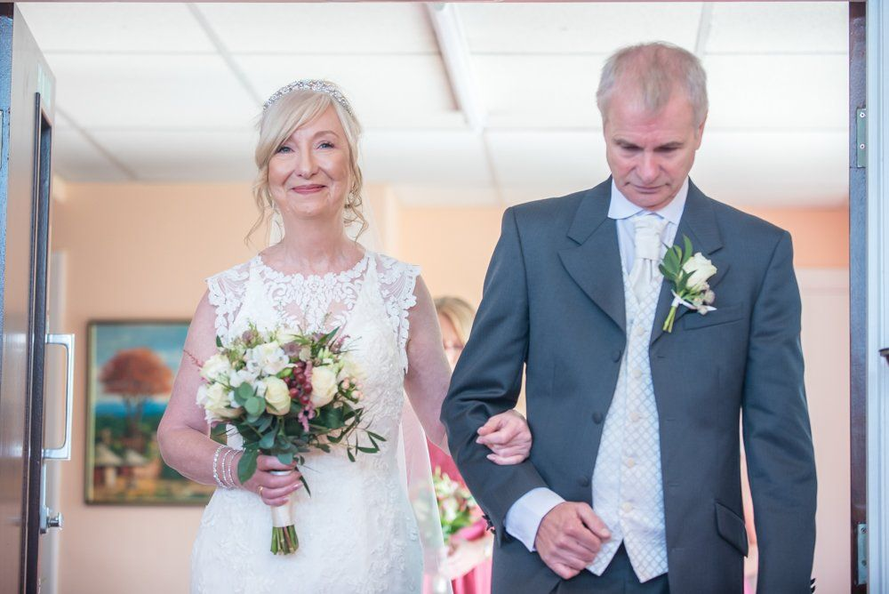 Caroline walking down aisle with her brother, Hotel Van Dyk wedding photography Chesterfield
