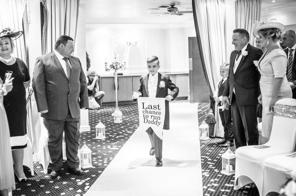 Bride's son walking down aisle with sign, Waterton Park Hotel weddings, Yorkshire wedding photographers