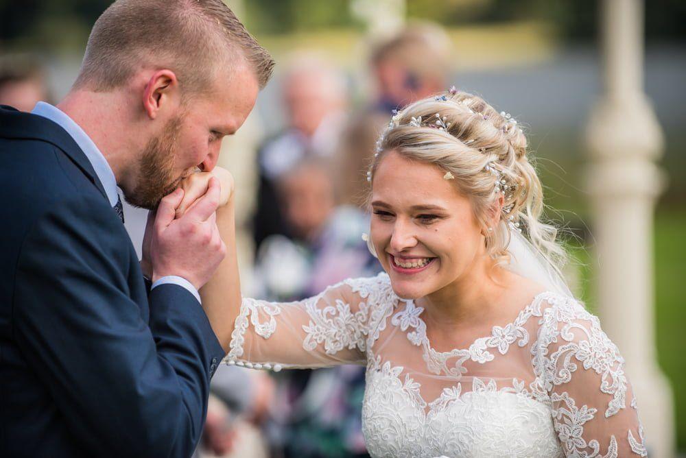 Groom kissing bride on hand, Inn on the Lake Weddings, Lake District