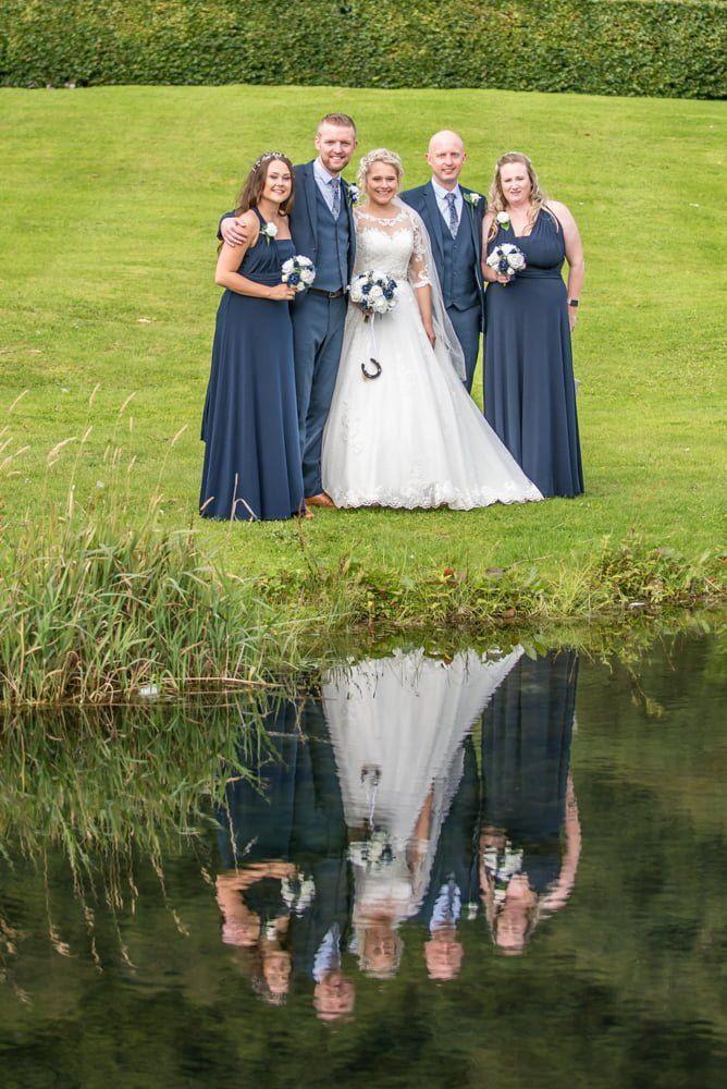 Bridal party reflection in mirror lake, Inn on the Lake Weddings, Lake District