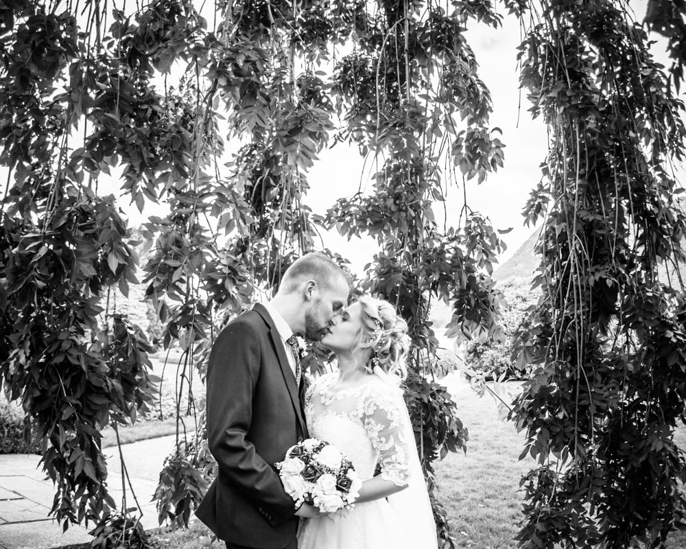 Bride and groom kissing in hotel grounds, Inn on the Lake Weddings, Lake District