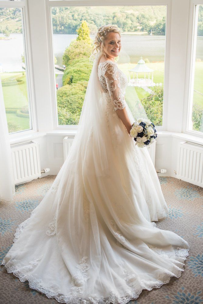 Sarah posing in window with her gown, Inn on the Lake Weddings, Lake District