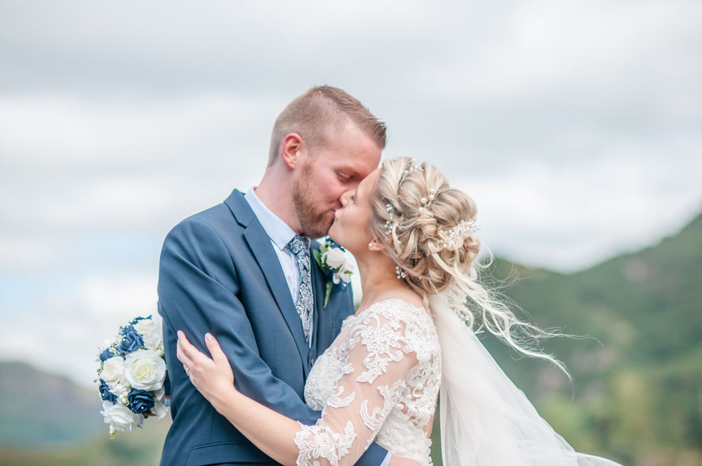 Kisses with fells in background, Inn on the Lake, Ullswater, Lake District documentary wedding photographers