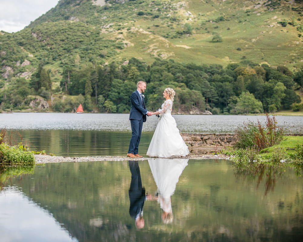 Holding hands on mirror lake, Inn on the Lake Weddings, Lake District