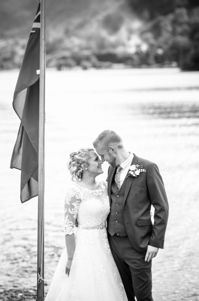 Bride and groom on boat with lake in background, Inn on the Lake, Ullswater, Lake District documentary wedding photographers