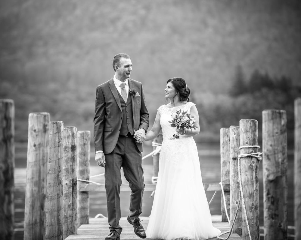Walking along jetty bride and groom, Lingholm weddings, Lake District wedding photographers