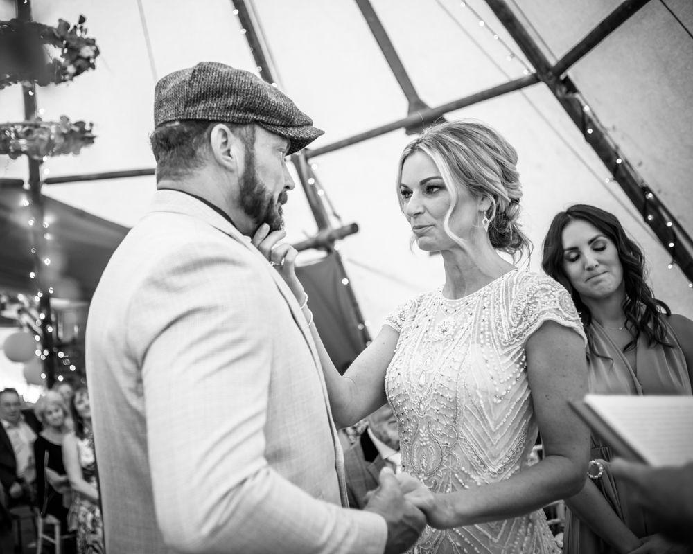 Bride reassuring groom in ceremony, Lancashire wedding photographer, tipi wedding