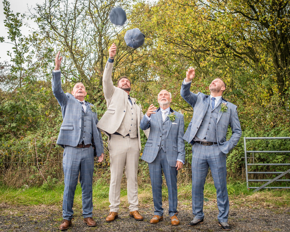 Groomsmen throwing flat caps, Lancashire wedding photographer, tipi wedding