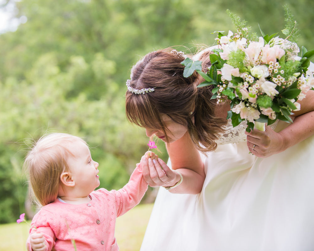 Flowergirl showing bride a flower, Merewood House, Windermere, Lake District wedding photographers