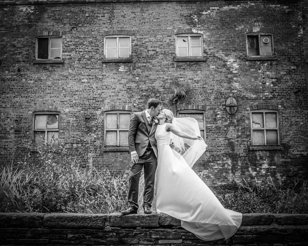 Bride and Groom on wall, Lake District female wedding photography