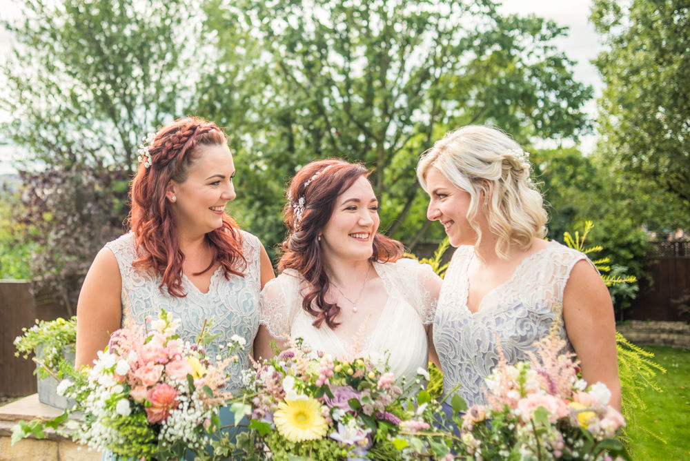 Bride and bridesmaids laughing together in sunshine Lake District wedding photography